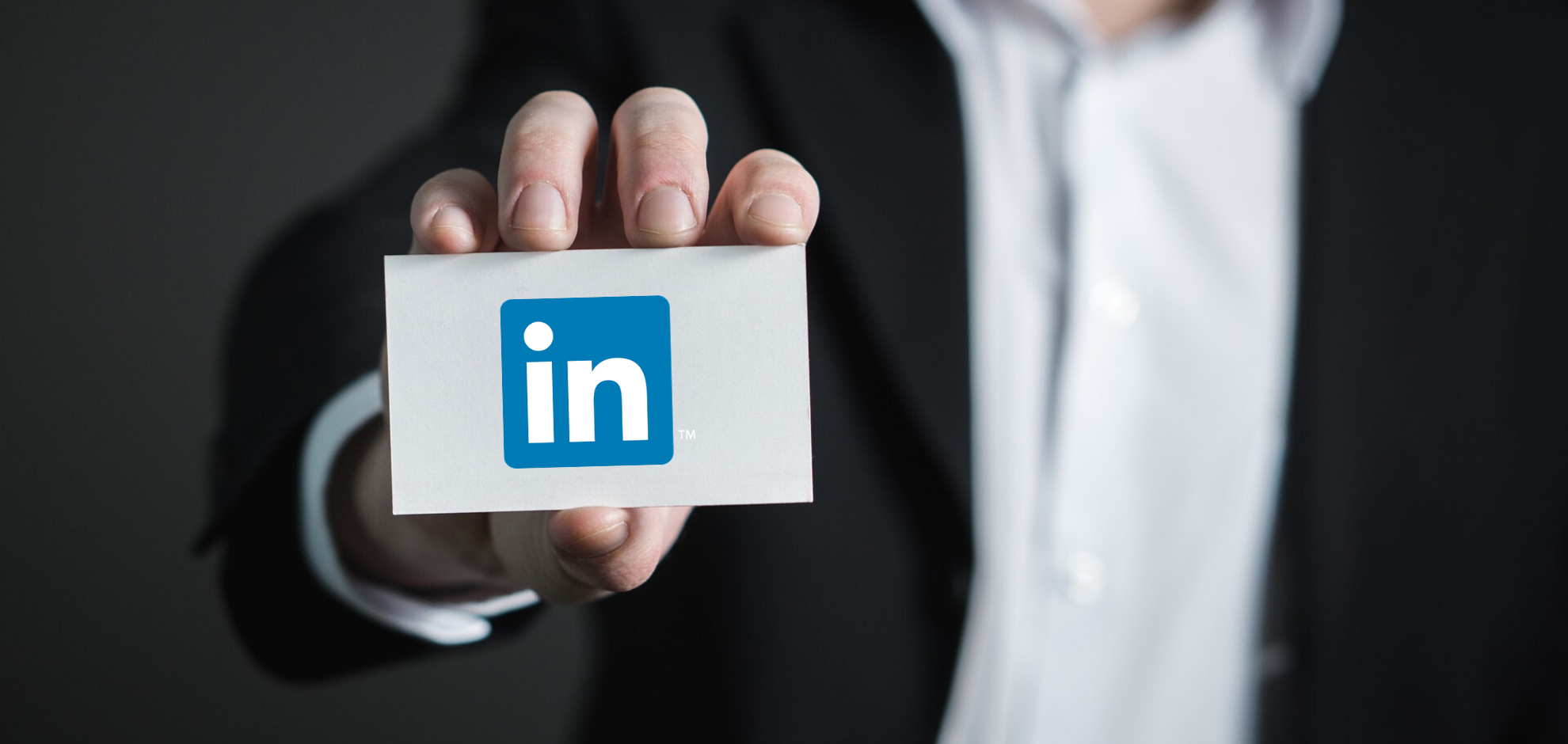 Man holding card with LinkedIn Logo
